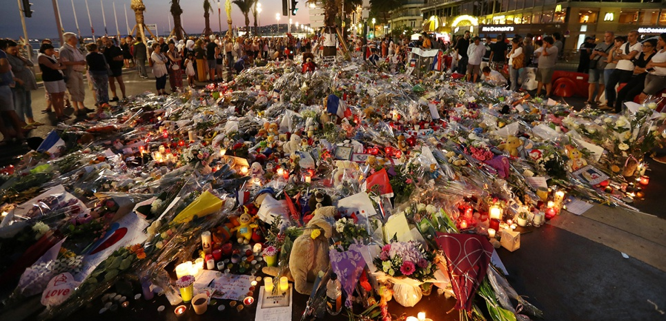 People stand in front of flowers, candles and messages laid at a makeshift memorial in Nice on July 18, 2016, in tribute to the victims of the deadly attack on the Promenade des Anglais seafront which killed 84 people. France was set to hold a minute's silence on July 18, 2016 to honour the 84 victims of Mohamed Lahouaiej-Bouhlel, a 31-year-old Tunisian who drove a truck into a crowd watching a fireworks display on Bastille Day, but a period of national mourning was overshadowed by bickering politicians. Church bells will toll across the country, and the country will fall silent at midday, a now grimly familiar ritual after the third major terror attack in 18 months on French soil. / AFP PHOTO / Valery HACHE